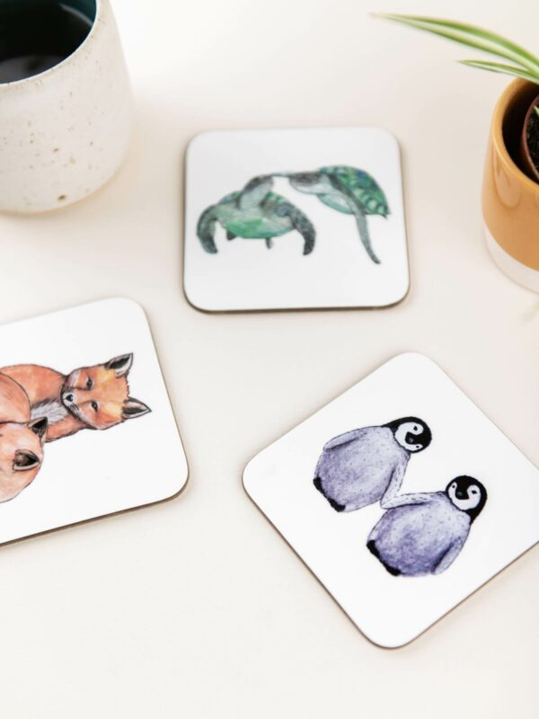 Illustrated coasters with animal couples: turtles, penguins and foxes, scattered on a table