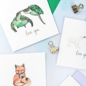 Selection of cards with pairs of animals illustrated and 'love you' hand lettered text printed beneath each couple.