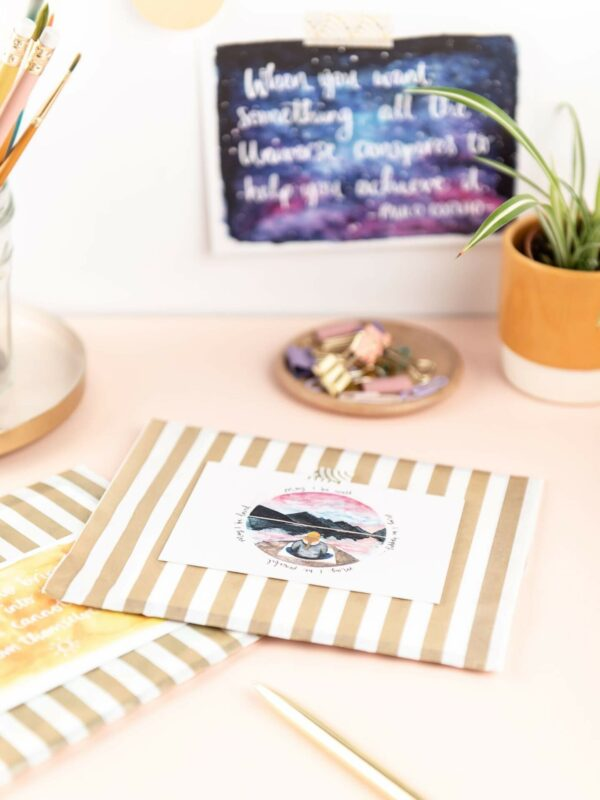 Desk set up with cards packaged in gold stripe bags and thank you note
