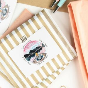 Desk set up with cards packaged in gold stripe bags and illustrated thank you notes