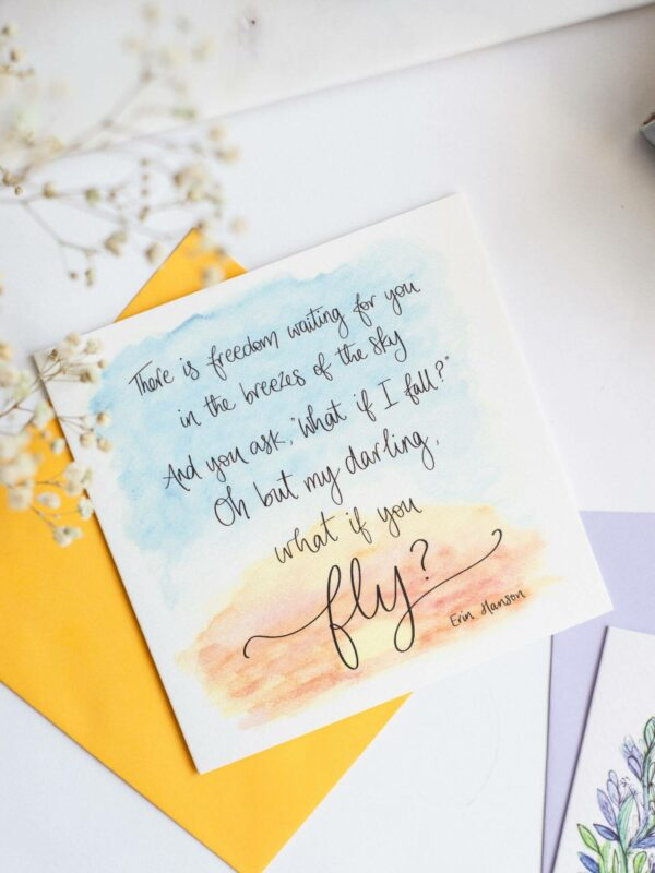 Hand lettered quote printed on a card over a sunrise sky watercolour design 'There is freedom waiting for you in the breezes of the sky, And you ask 'what if I fall?' Oh but my darling, what if you fly? Erin Hanson'