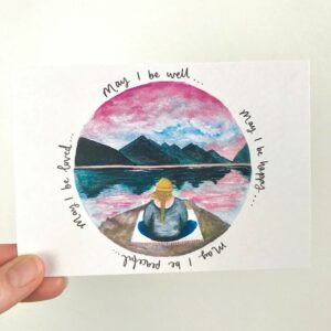 Postcard with illustration of meditating girl sat beneath mountains, with hand lettered words 'May I be well... may I be happy... may I be peaceful... may I be loved'.