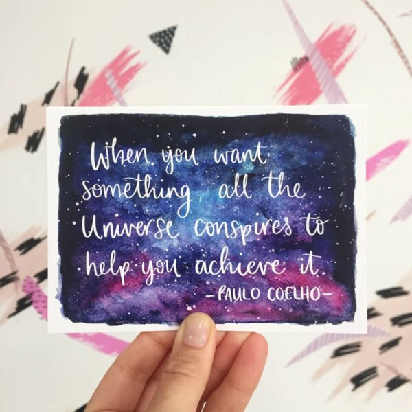 Postcard with quote written on night sky watercolour: 'When you want something, all the universe conspires to help you achieve it - Paulo Coelho'