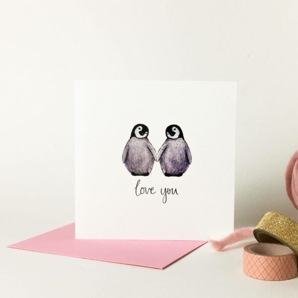 Printed card - two cute fluffy penguins holding flippers and text 'love you' beneath