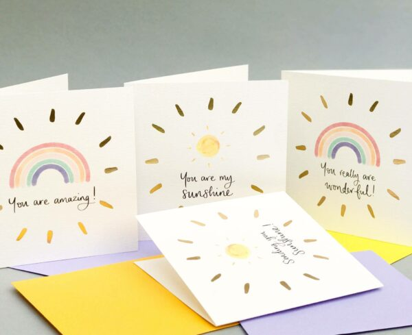 Positive greetings card designs with sunshines, rainbows, positive quotes and gold foil detailing