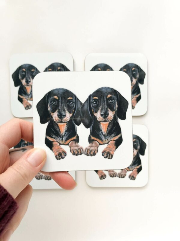 Stack of coasters with illustrated design of 2 cute black and tan sausage dogs
