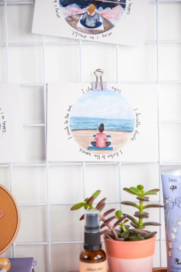 Illustrated postcard with meditation design and words reading 'I close my eyes, I breathe deeply, I listen to the waves, I smile to the sun.'