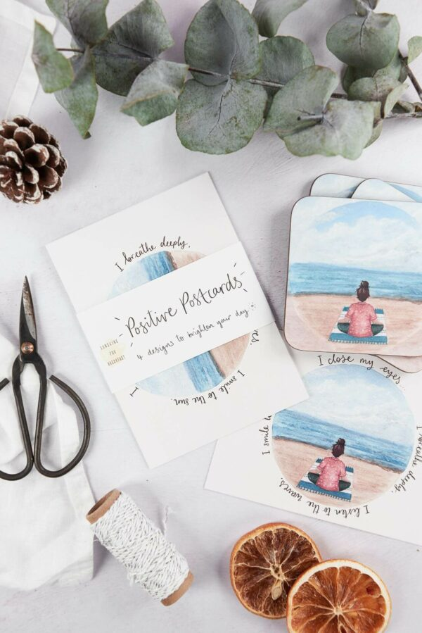 Matching postcards and coasters with meditation by the beach design on a festive table set up