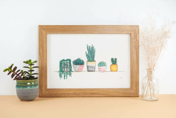 Framed print with cute little house plants and succulents on a shelf.