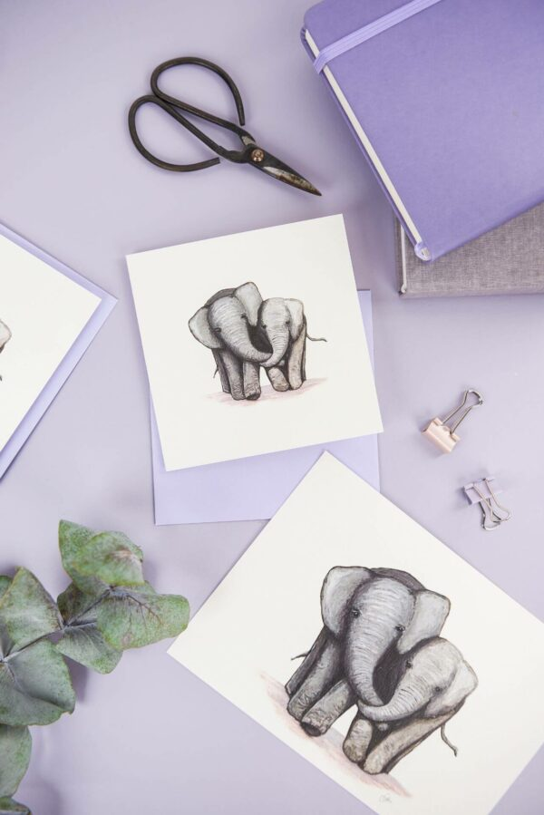 Matching cute elephant illustrated art print and card on a pretty purple desk