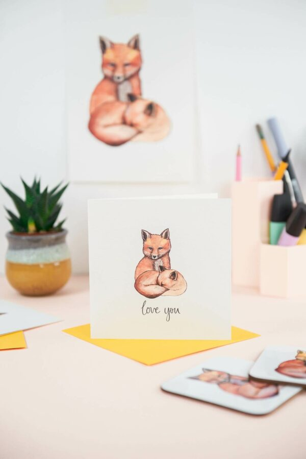 Illustrated card of 2 foxes and hand lettered text 'love you' printed beneath, plus matching art print in the background