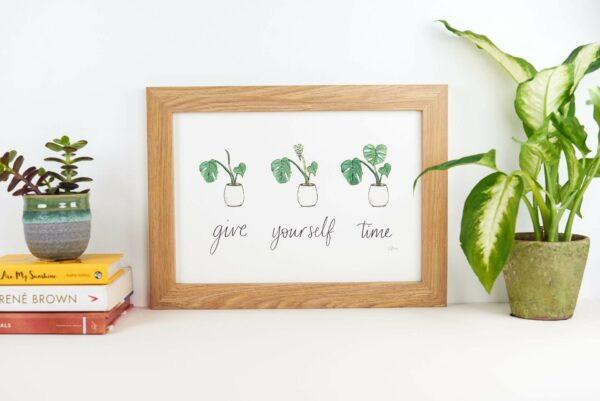 Framed print with hand lettered text 'give yourself time' and illustrations of a slowly uncurling monstera plant