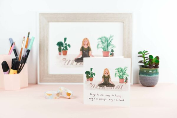 framed art print of a girl calmly meditating surrounded by house plants, with a matching card design and quote reading 'may I be well, may I be happy, may I be peaceful, may I be loved'.
