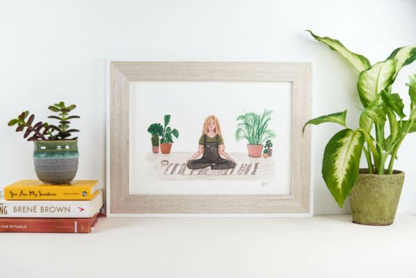 framed art print of a girl calmly meditating surrounded by house plants.