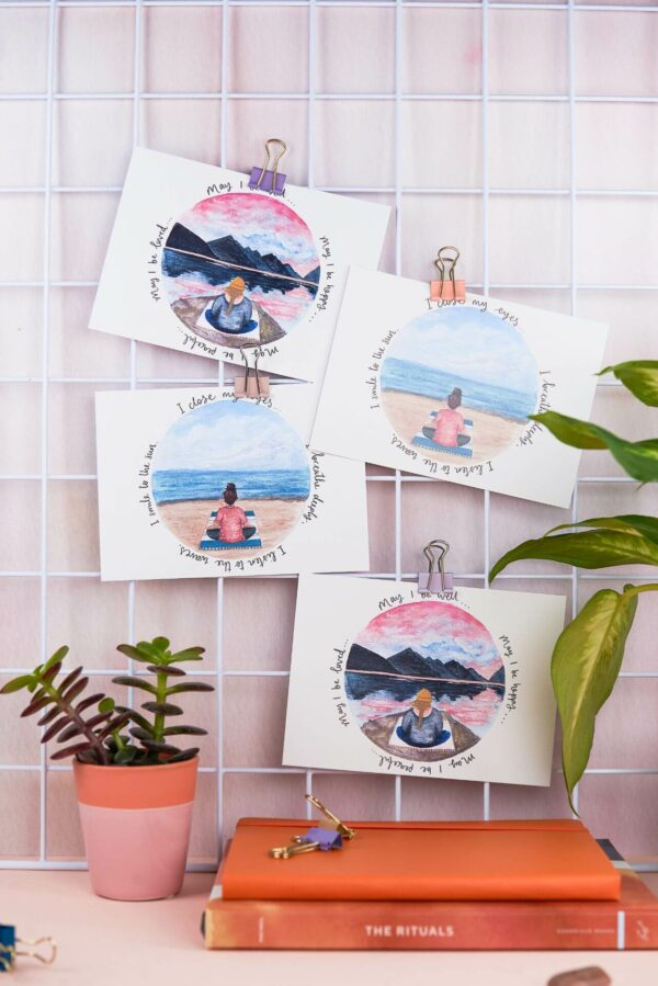 4 meditation postcards pinned up on a home office desk.