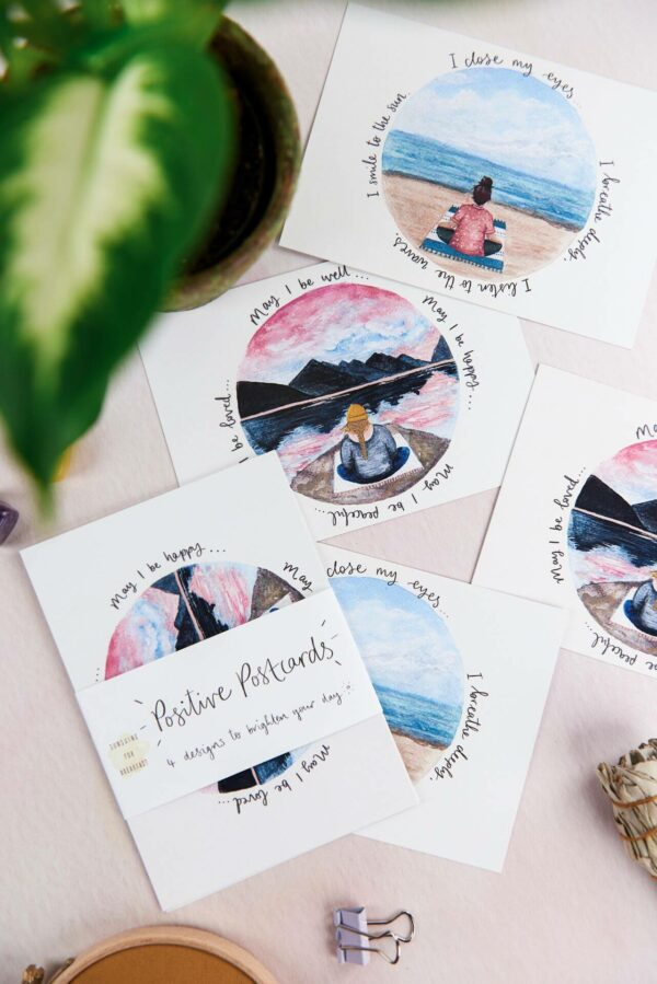 Positive postcards with meditation theme illustrations and quotes scattered on a table