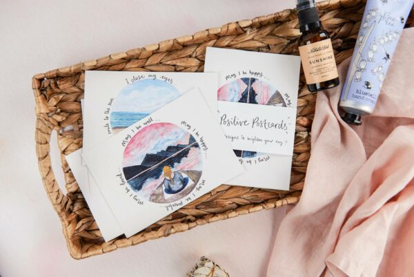 Positive postcards with meditation theme illustrations and quotes, in a basket with Nathalie Bond Sunshine oil and BlueFayre handcream