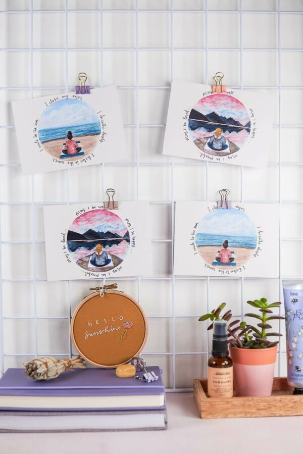 Positive postcards hanging from a pretty desk display with meditation theme illustrations and quotes