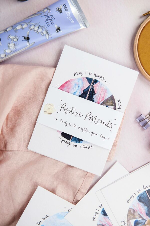Pack of positive postcards by Sunshine for Breakfast, scattered on a table with a soft linen scarf and BeeFayre handcream