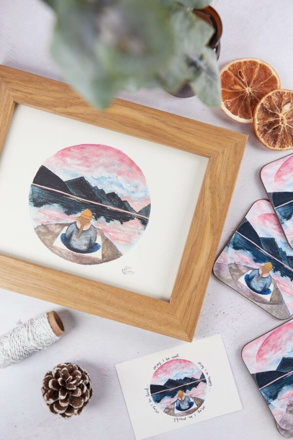 Meditation illustration of a girl sat beneath pretty pink sunset and mountains, with matching postcard and coasters.