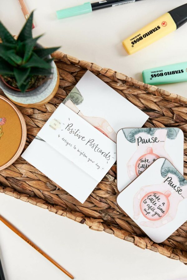 Positive postcard designs on a desk with matching coaster that reads 'Pause... take a little time to refill your cup'