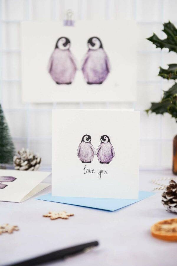 Illustrated card with 2 cute fluffy penguins and text 'love you' printed underneath, with matching art print, on a pretty festive desk set up