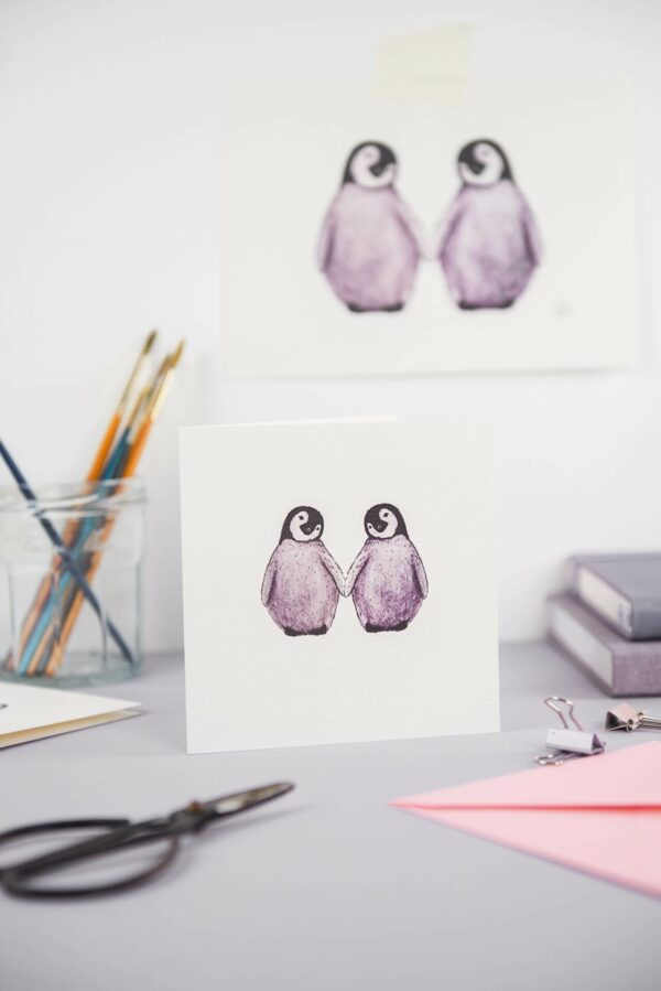 Illustrated card with 2 cute fluffy penguins, with matching art print, on a pretty desk set up
