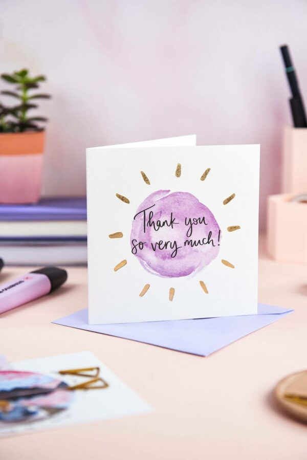 Pretty desk featuring 'thank you so much' card with simple purple design and gold foil detail