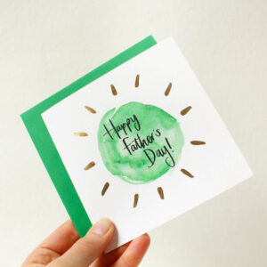 A hand holding a Father's Day card in simple green and gold design.